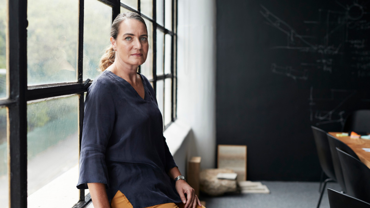 Portrait of mature female entrepreneur sitting by window in board room at workplace