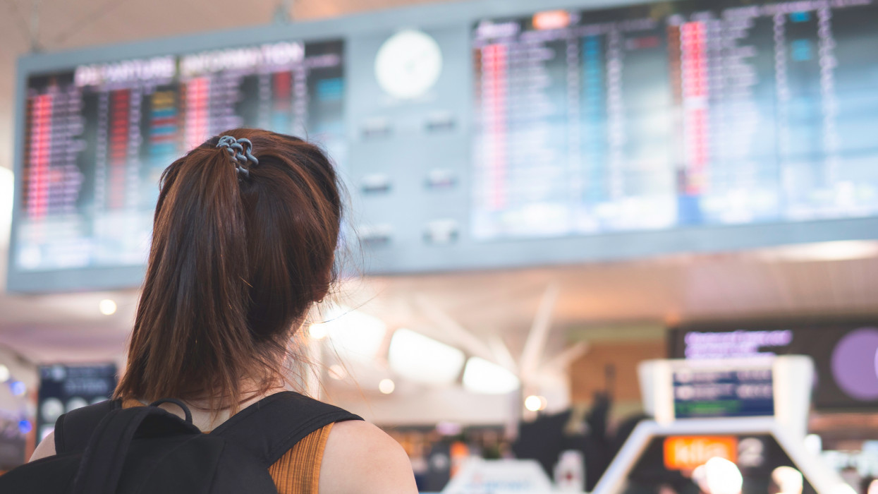 Young asian woman standing in front of flight timetable board in  airport
