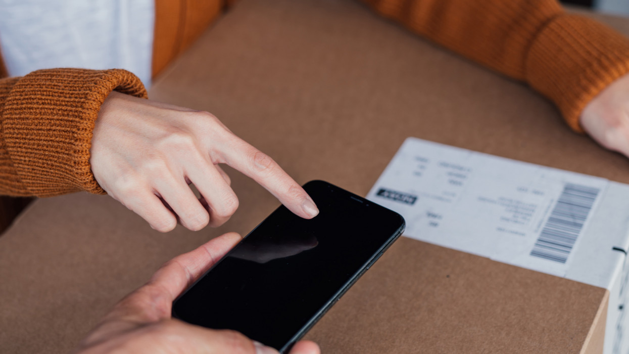 Close-up of young woman holding a carton box, signing for her delivery on a digital device from the courier. Home delivery service makes life easier. Online shopping concept.