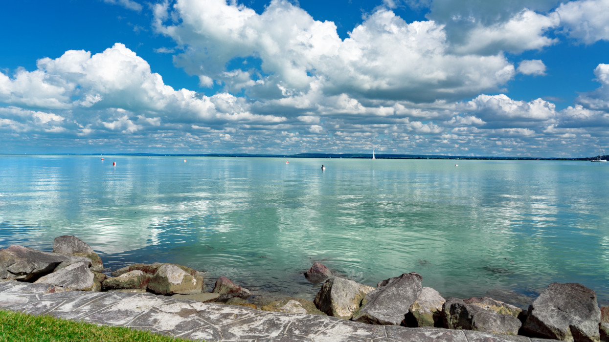 simple picture about Lake Balaton in Hungary from Badacsony beach with blue sky and cloud refletion on the water .