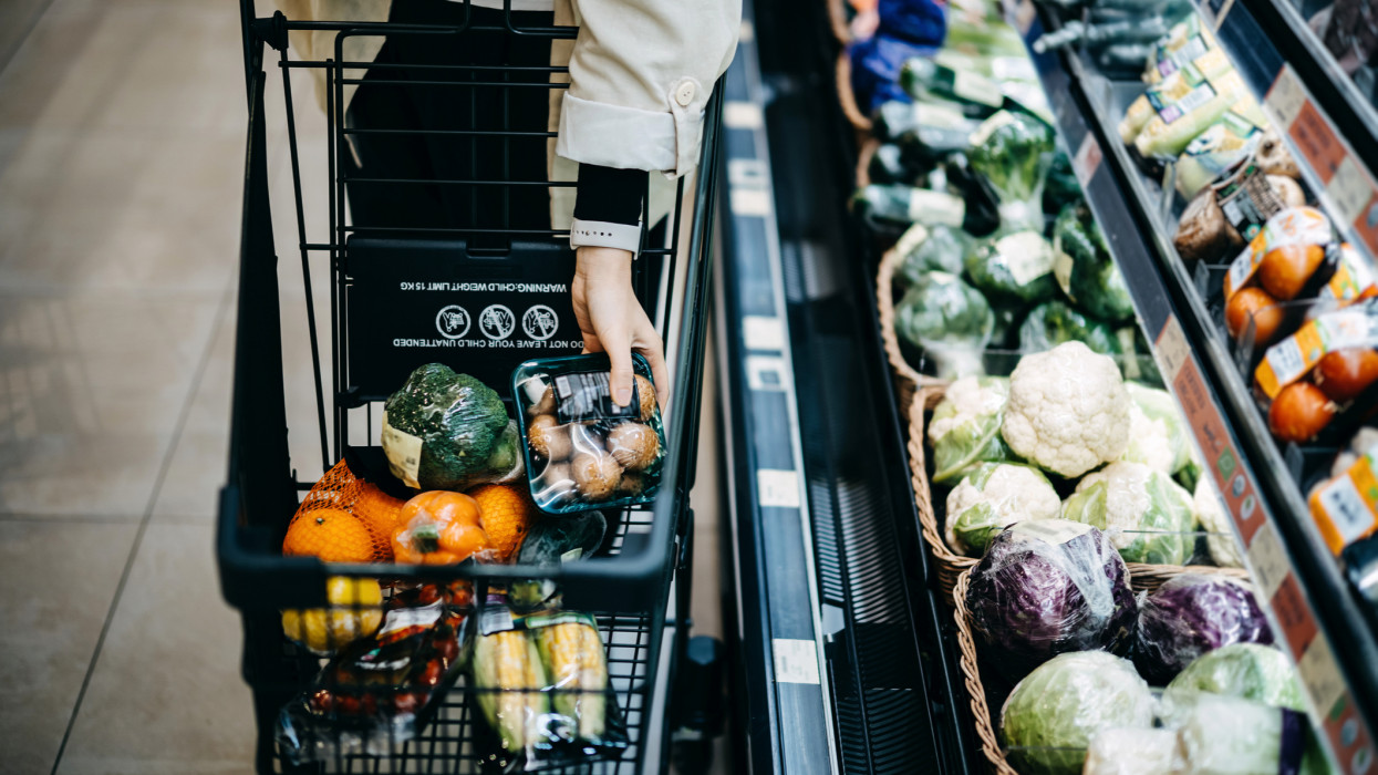 Close up of womans hand shopping for fresh groceries in supermarket and putting a variety of organic vegetables in shopping cart