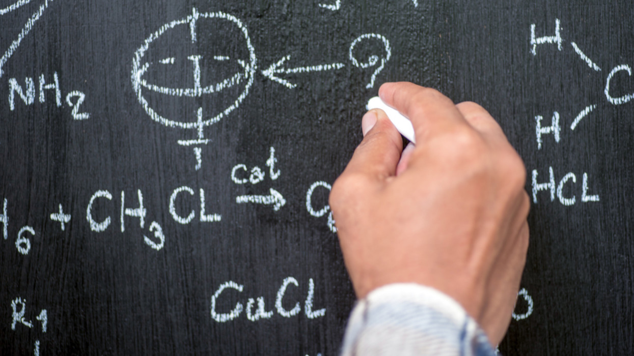 A man with a white hand holding a blackboard formula