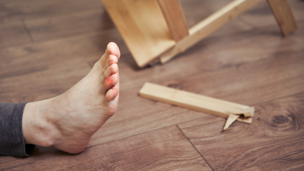 A man injured his toe after falling from a wooden stepladder. Ladder made of wood broke under a man while working at home