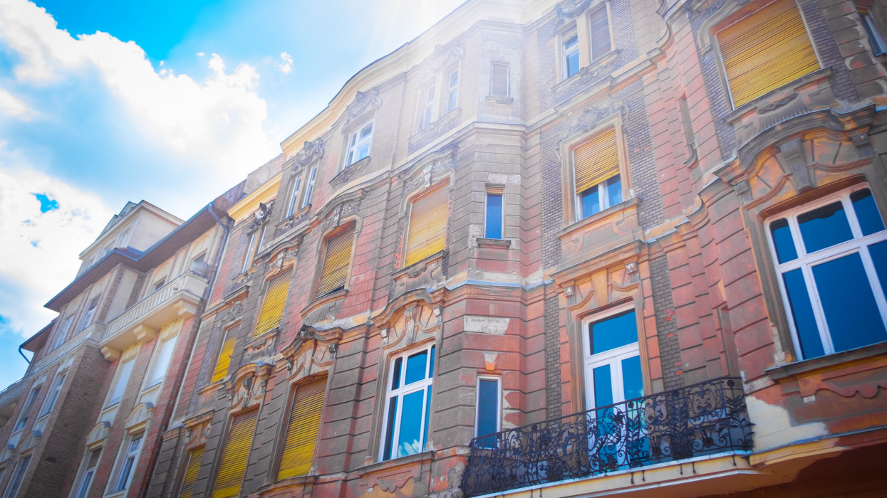 Brick building with yellow window shades in Budapest Hungary