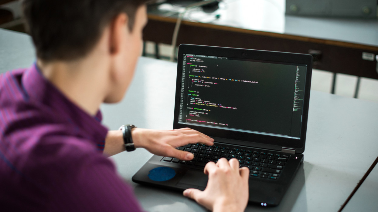 Young man using his laptop to try to solve problem with code. Computer programmer working on new code. Software problem