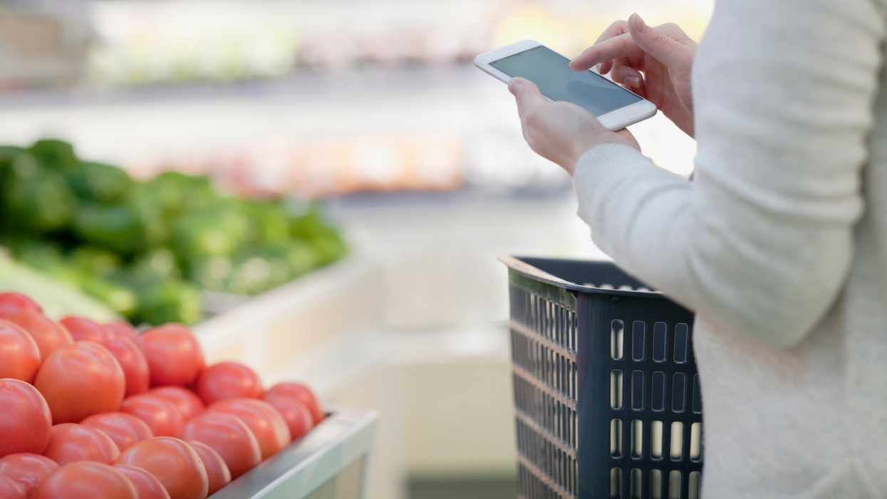 Hand on smart phone in supermarket produce aisle