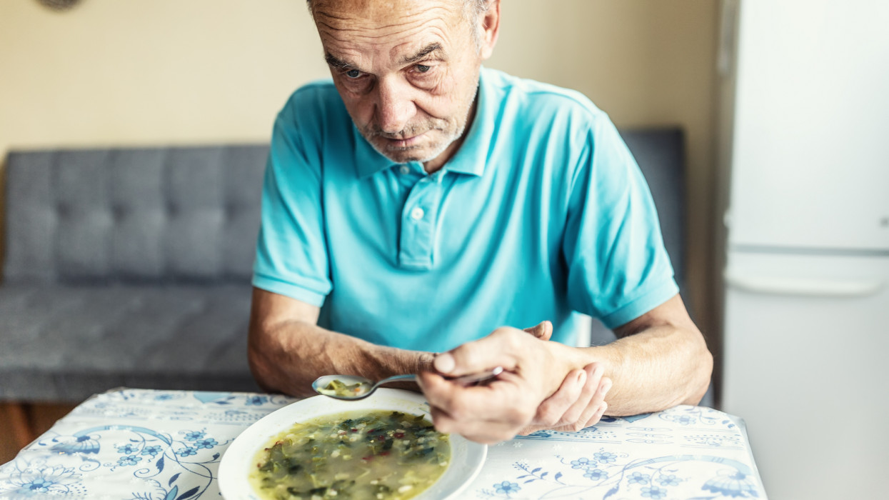 Old man with a Parkinson disease holds his arm with a hand, trying to eat a soup.