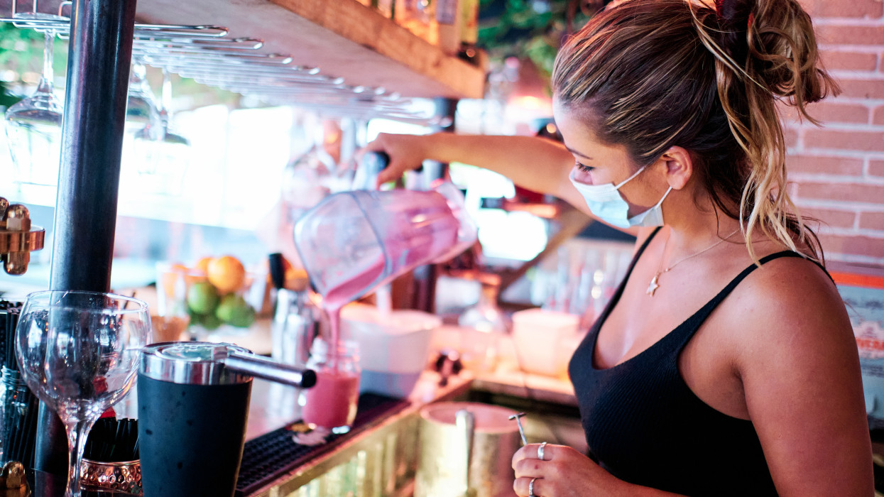 waitress with face mask preparing a cocktail at the restaurant - coronavirus and small business concept