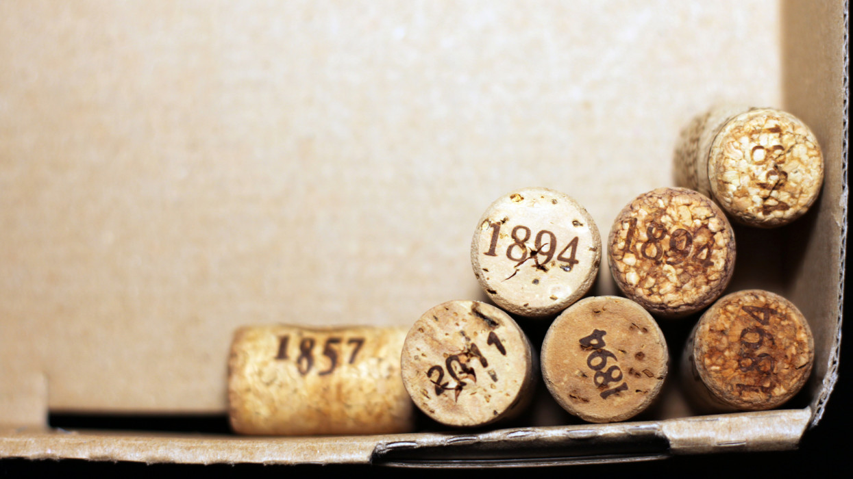 Used wine corks from various varieties of vintage red wine and vintage white wine depicting different dates and years of wine making or creating winery on brown paper background from wine box