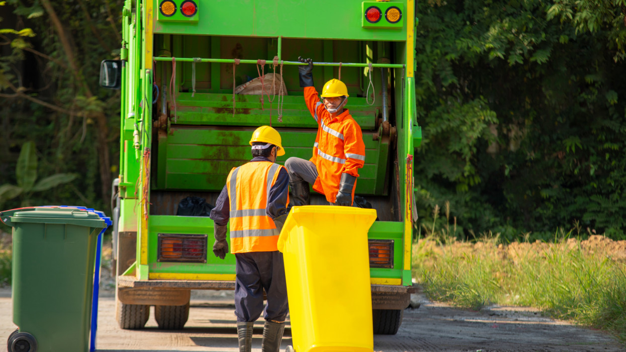 Two garbage men working together on emptying dustbins for trash removal,Rubbish cleaner man working green truck trash.
