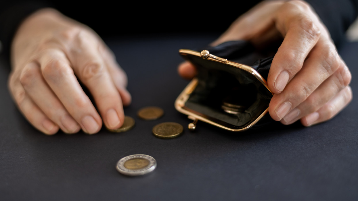 The hands of an elderly woman take out the last coins from the savings in a black wallet, the concept of poverty