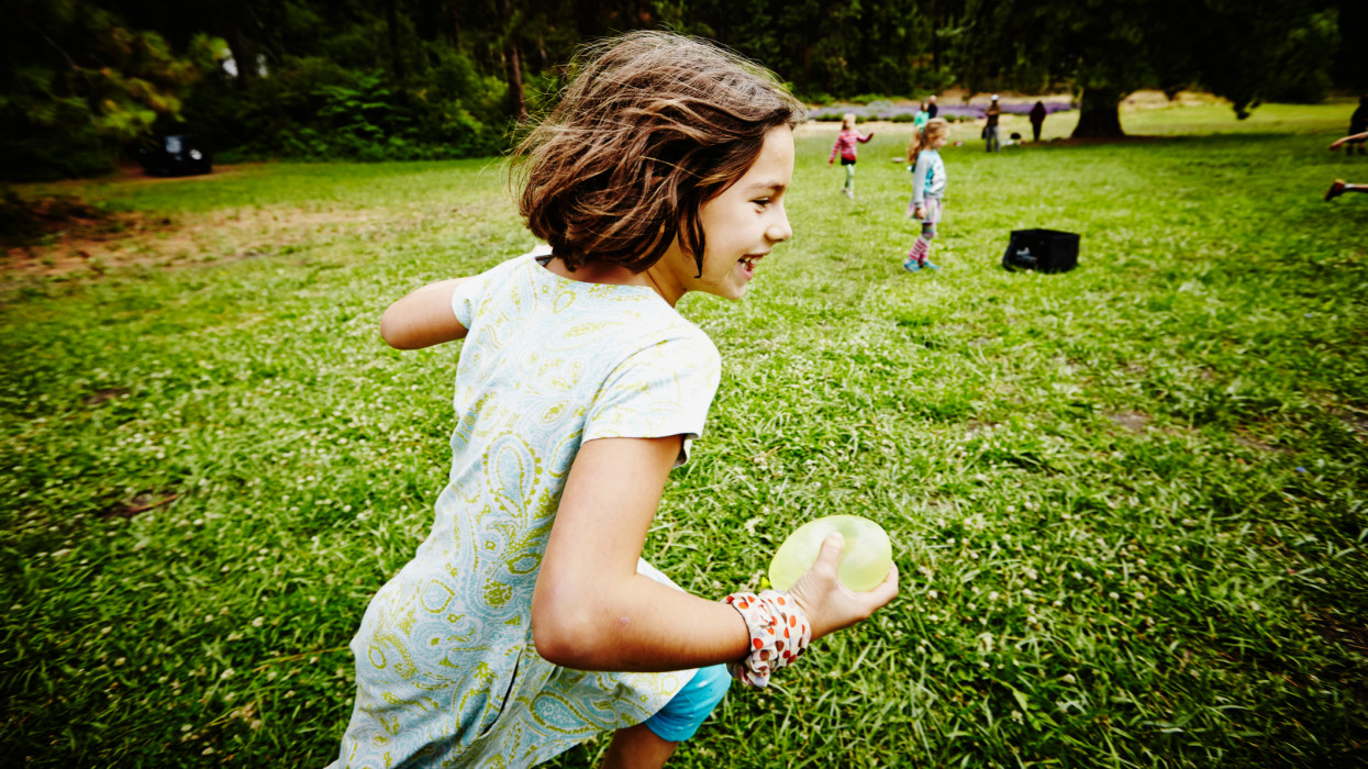 Smiling young girl running through grass field with water balloon during water balloon fight at summer camp