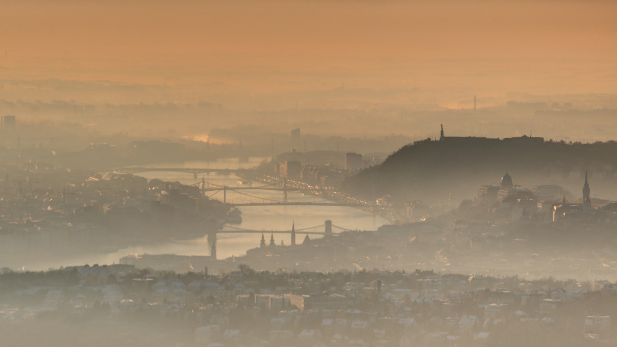 Downtown Budapest capital at sunrise in glowing winter morning mist and clouds with bridges over curving Danube river and Gellert Hill with Liberty Statue and Castle Hill at Buda side, Hungary Europe