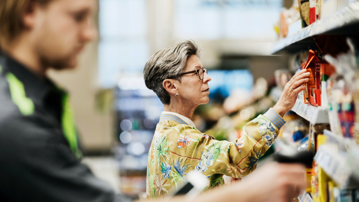 A senior woman picking some goods from the shelf while out shopping for groceries at her local supermarket.