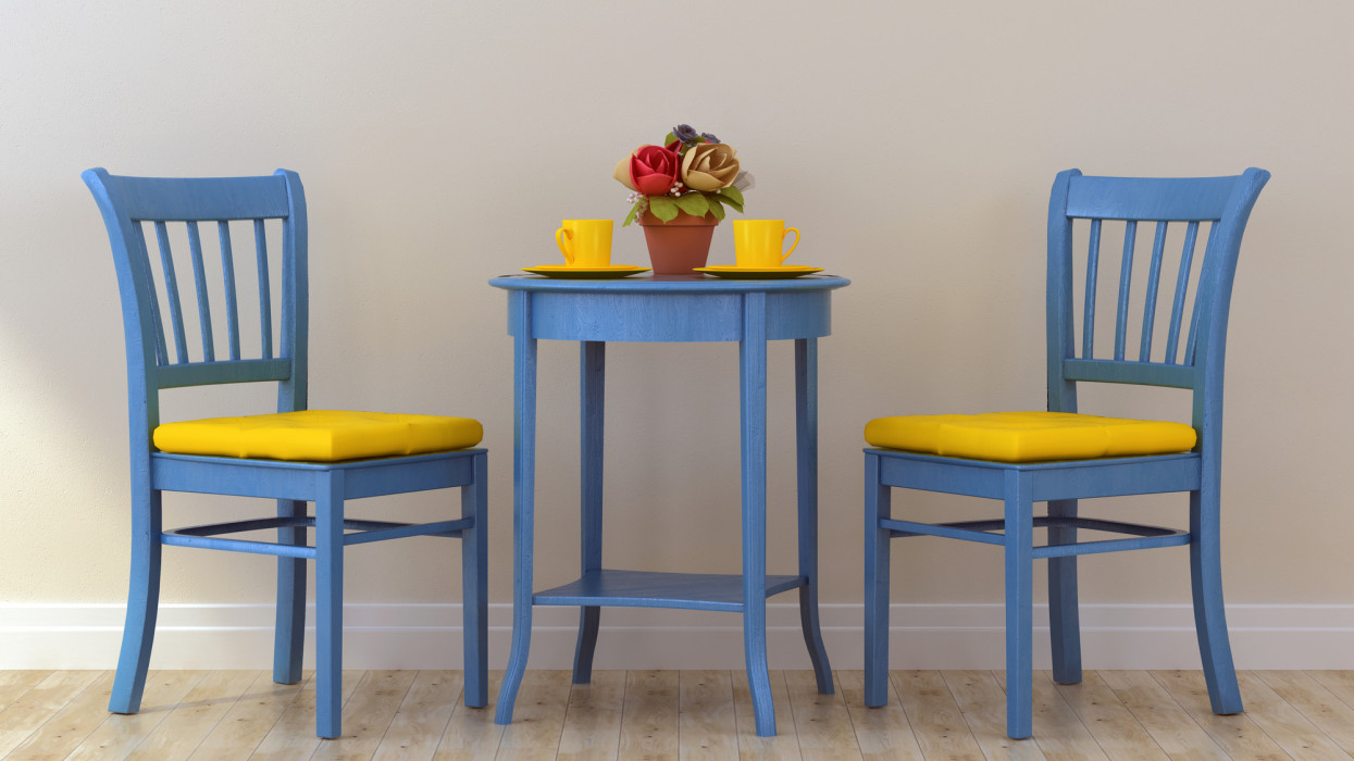 Two blue chairs with yellow cushions and blue coffee table against a white wall