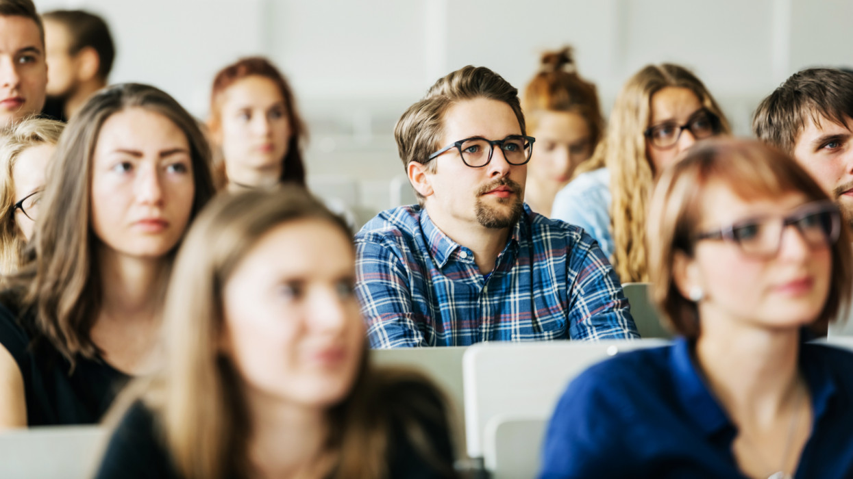 A group of young university students concentrating carefully on their professor during a lecture.
