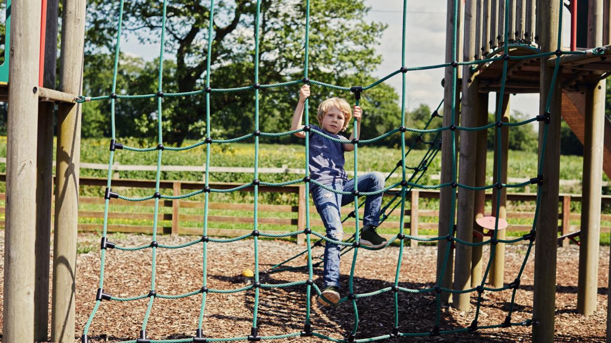 Boy climbing a rope climbing frame in the park