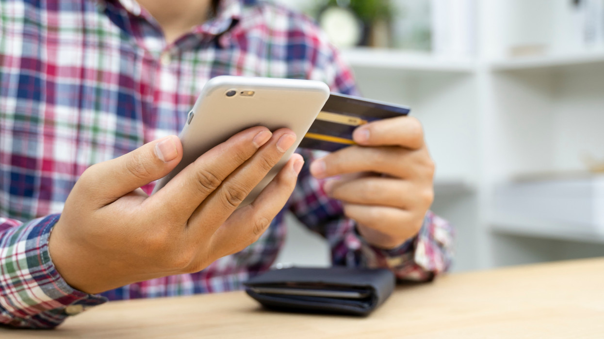 Young man hands holding credit card and using phone