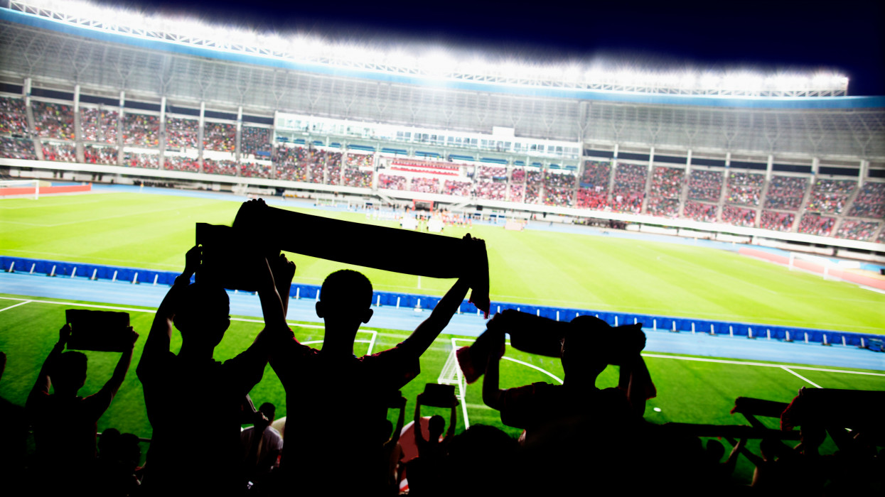 Passionate fans cheer and raise banners at a sporting event in the stadium