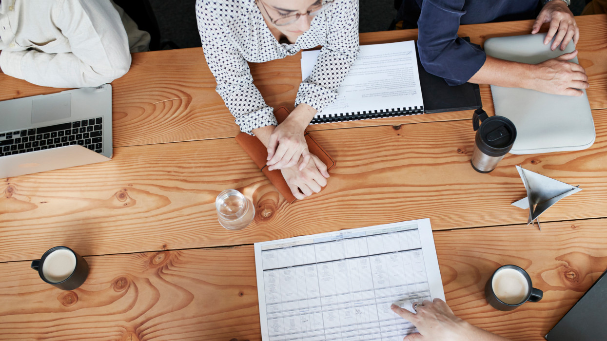 High angle view of business people discussing over blueprint at conference table in office