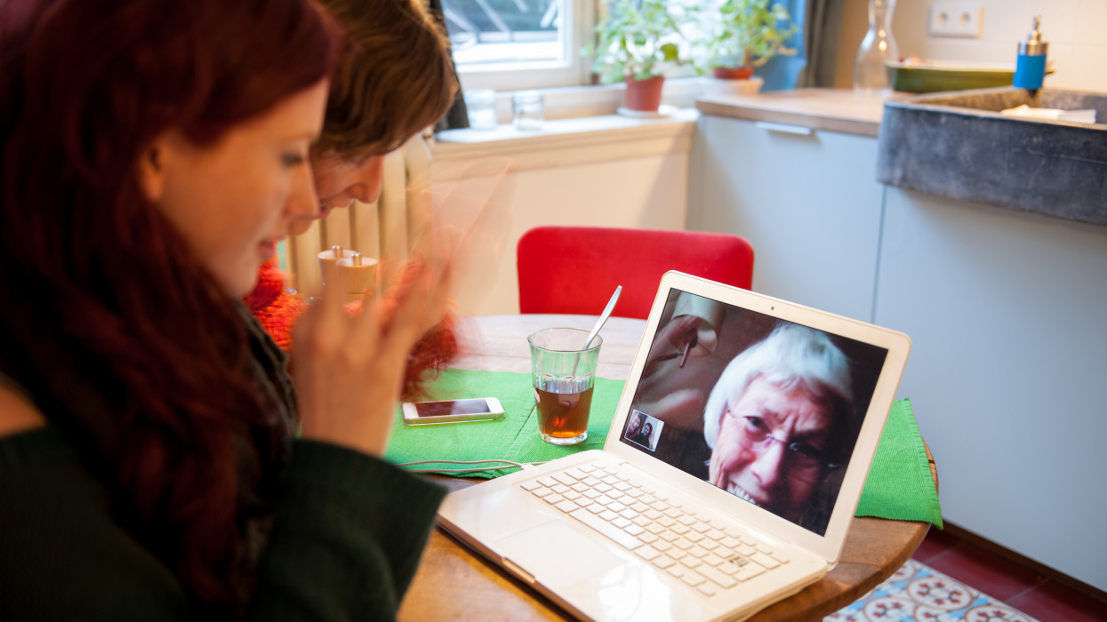 Two women having a video call on a laptop with their (step grand-) mother.