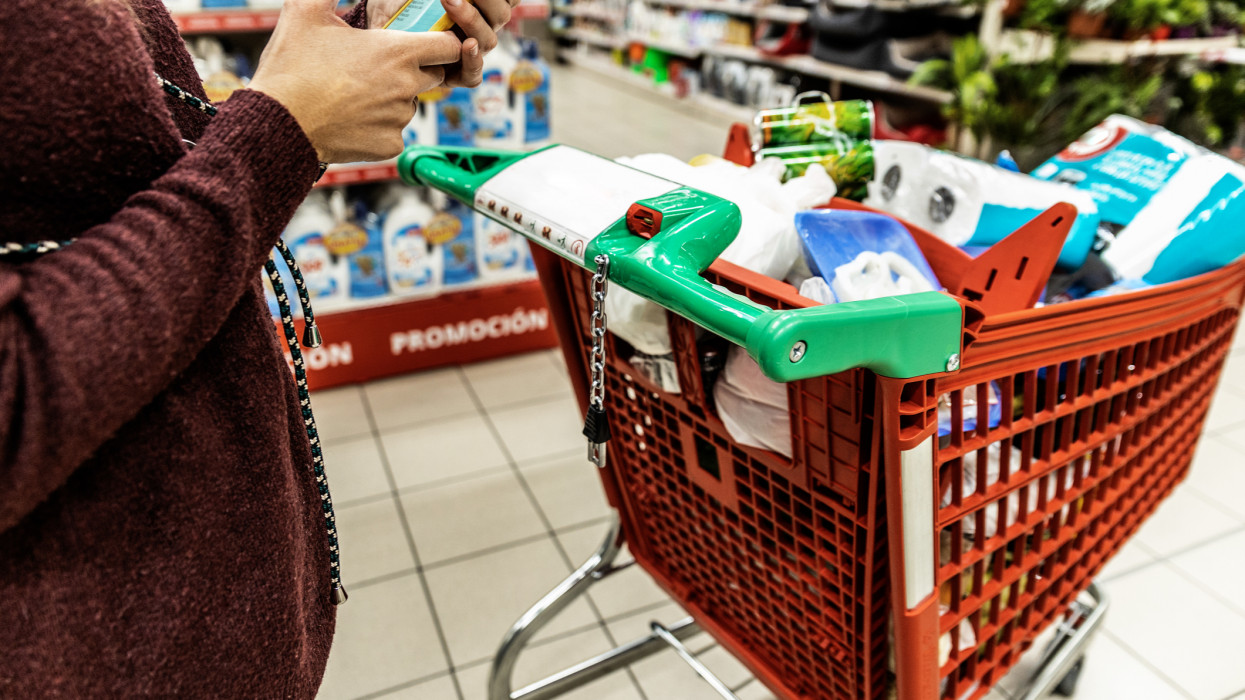 Woman viewing shopping list on her smartphone with full grocery cart. shopping concept