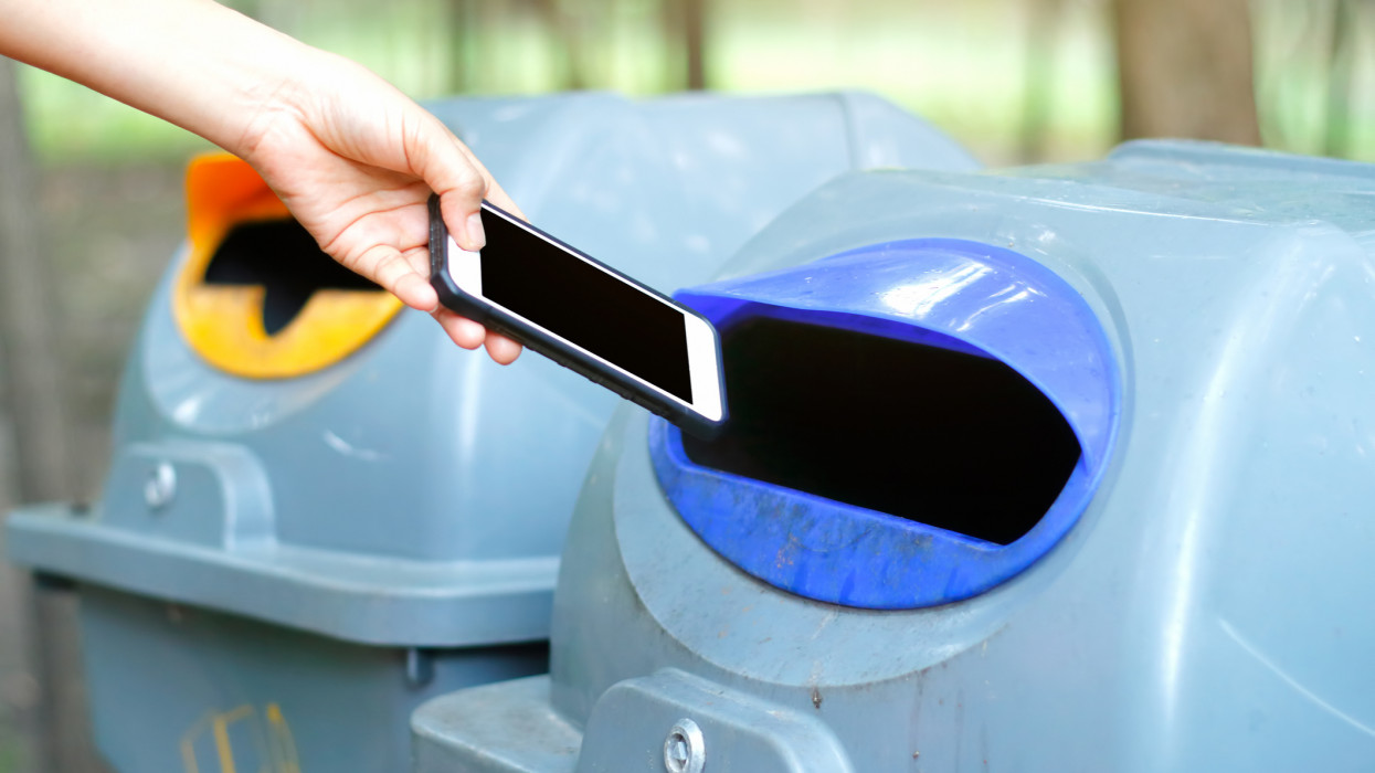 Woman throwing a phone into the trash