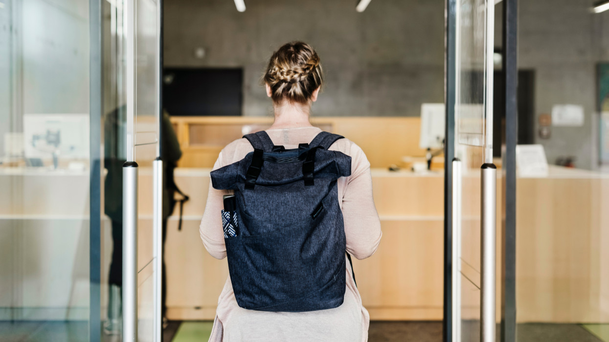A woman wearing a backpack walking through the entrance to a public library,