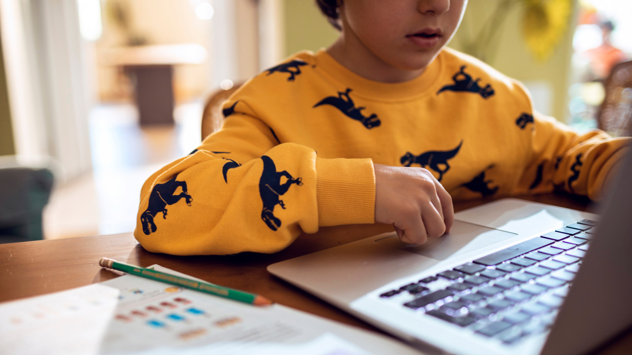 Close up of a young boy studying and doing homework using his laptop