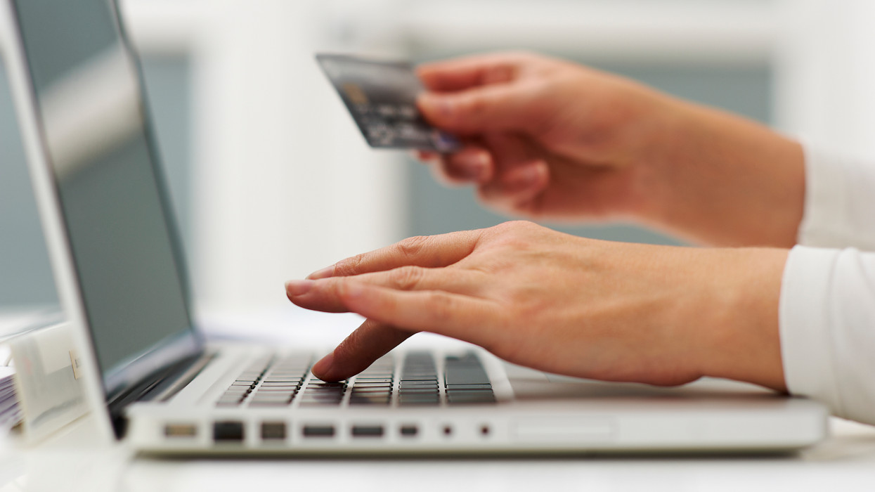 Woman using laptop computer and credit card to do shopping.