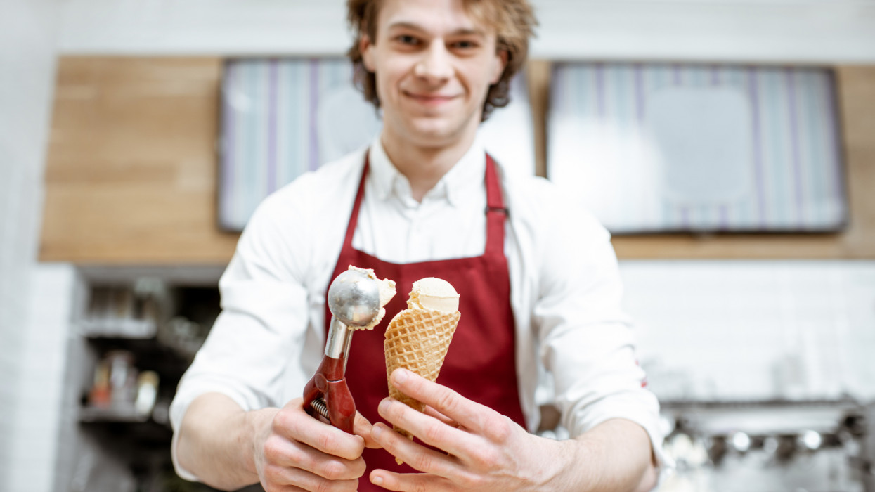 Young salesman putting ice cream ball into the waffle cone with professional tool at the pastry shop
