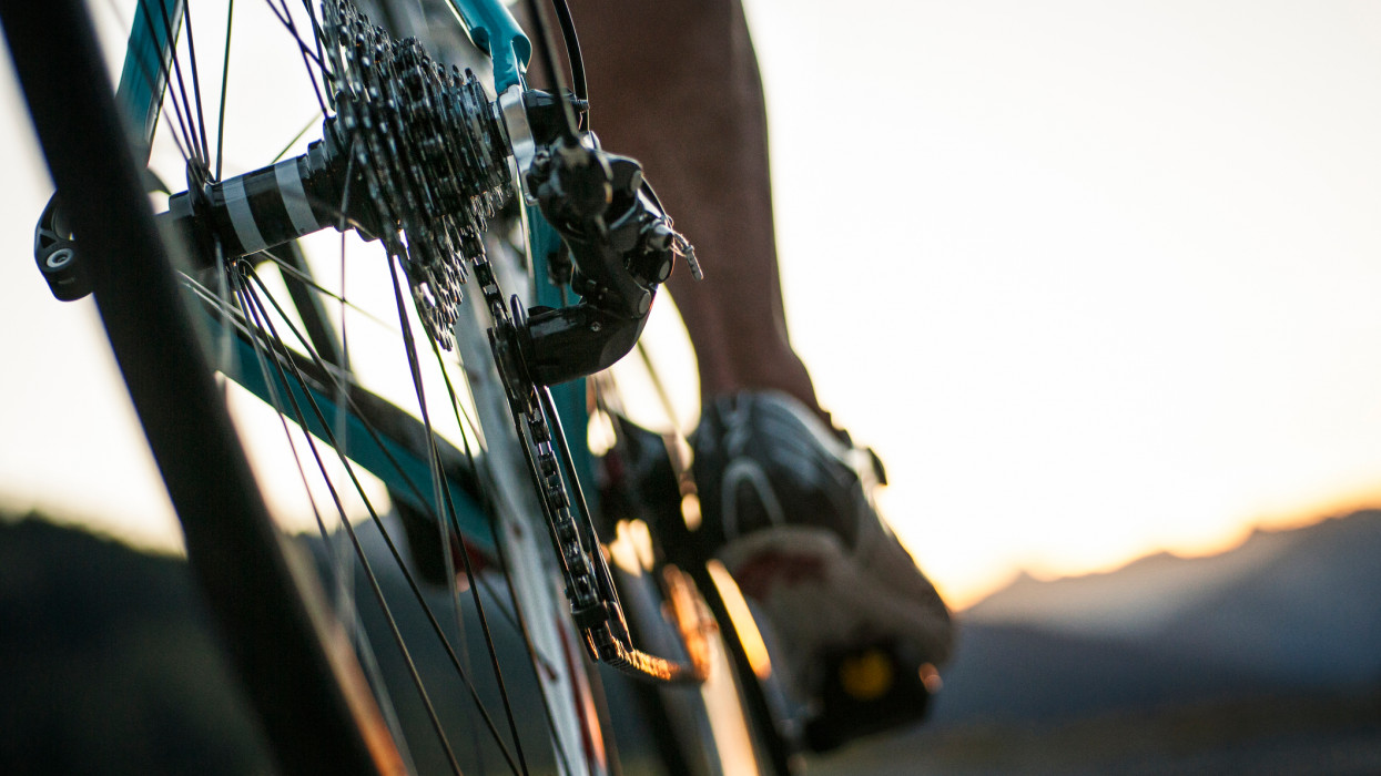 Closeup of a road cyclist riding towards sunset.