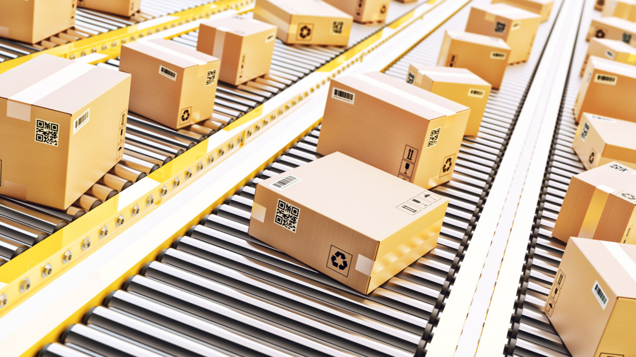Cardboard boxes on a conveyor line in distribution warehouse