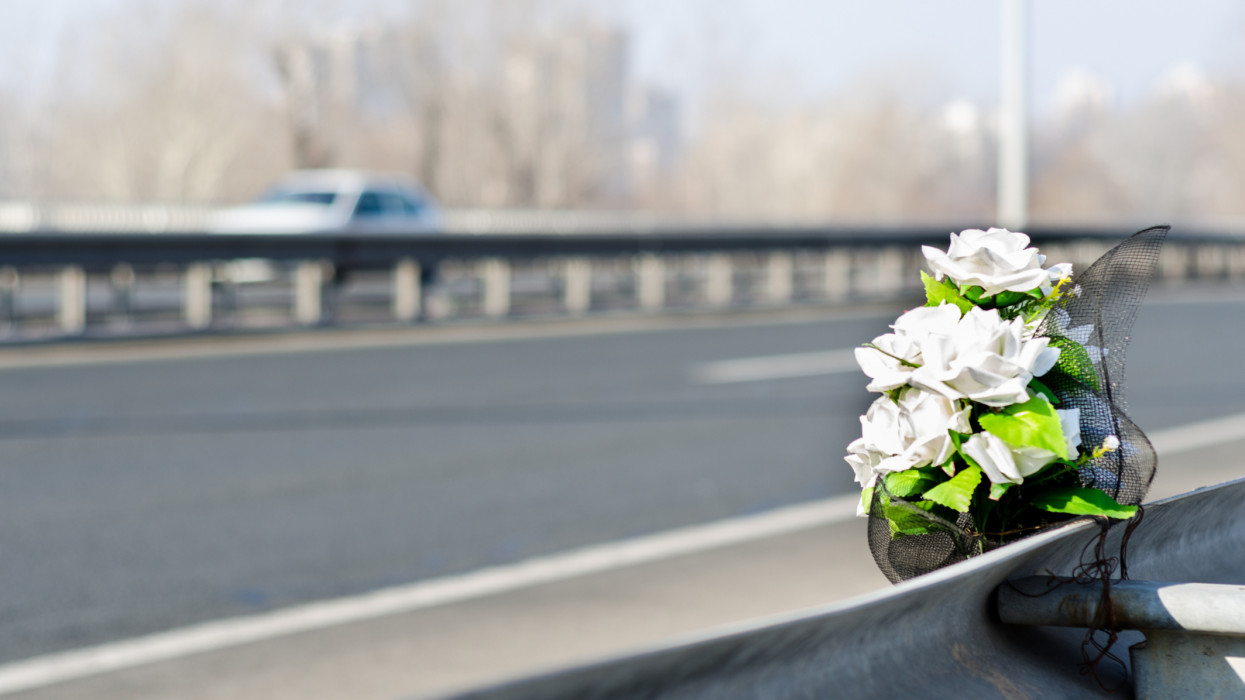 Artificial white roses flowers on the site of a traffic accident with a fatal outcome.