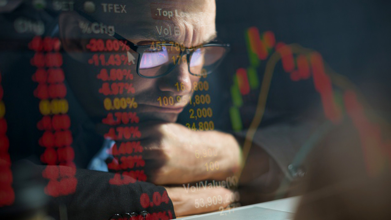 Businessman checking stock market data on computer screen and contemplating cimlapi