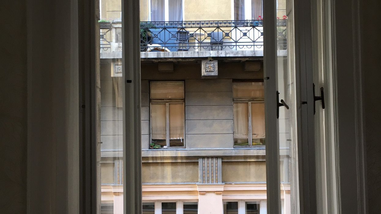 The photo looks through a double-pane window to the apartment building across the street.