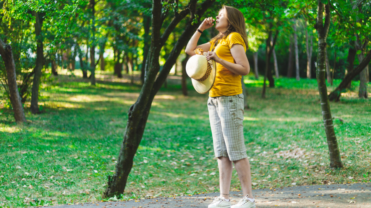 Young woman sneezing from seasonal allergic reaction in the park - Casually dressed girl with summer hat having flu symptoms while walking outdoors