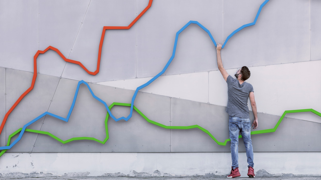 A young man holds onto a graph as it rises upwards indicating growth in a market and his rise with it, tracKing the financial markets