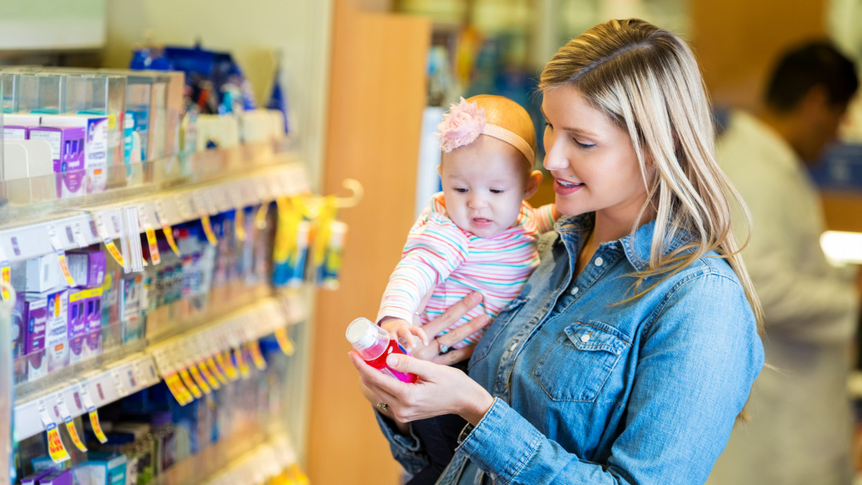 Mid adult Caucasian woman is purchasing childrens fever or cold medicine from local pharmacy. Mother is holding 4 month old baby girl. She is reading label on bottle of liquid childrens medicine.
