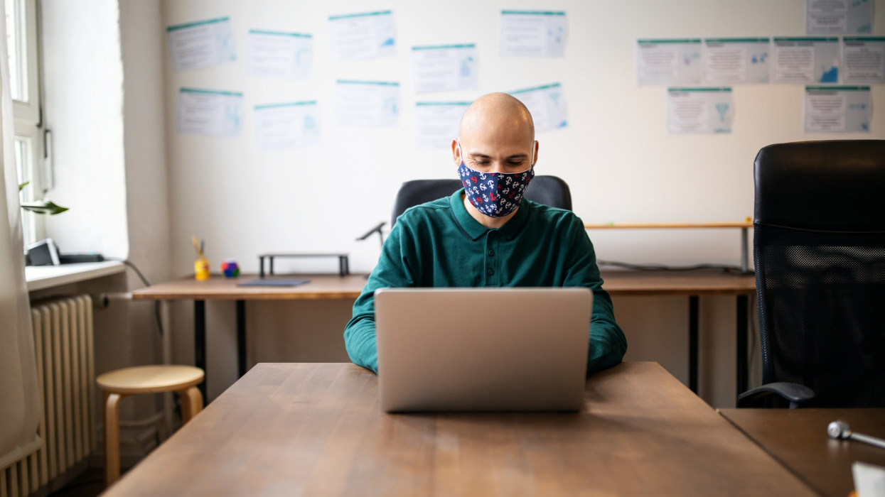 Male professional with face mask working in office. Businessman return to office after covid-19 pandemic lockdown.