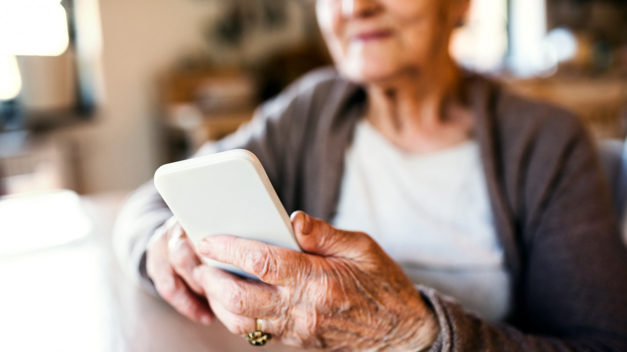 Beautiful grandmother at home sitting at the table and using smart phone.