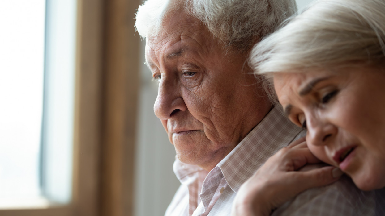 Worried middle aged woman embracing upset old man from back, side view head shot close up portrait. Sensitive mature wife showing support, comforting depressed elder husband, experiencing grief.