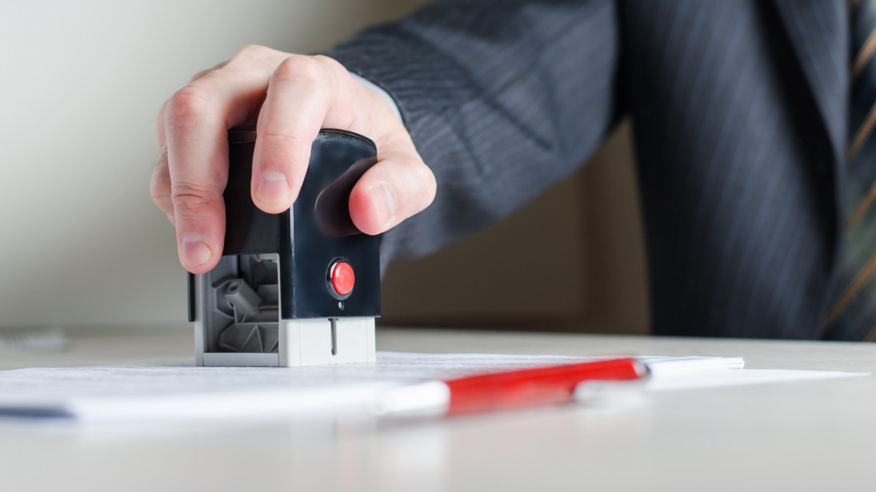 A lawyer or notary puts a seal on the document. A stamp in a mans hand