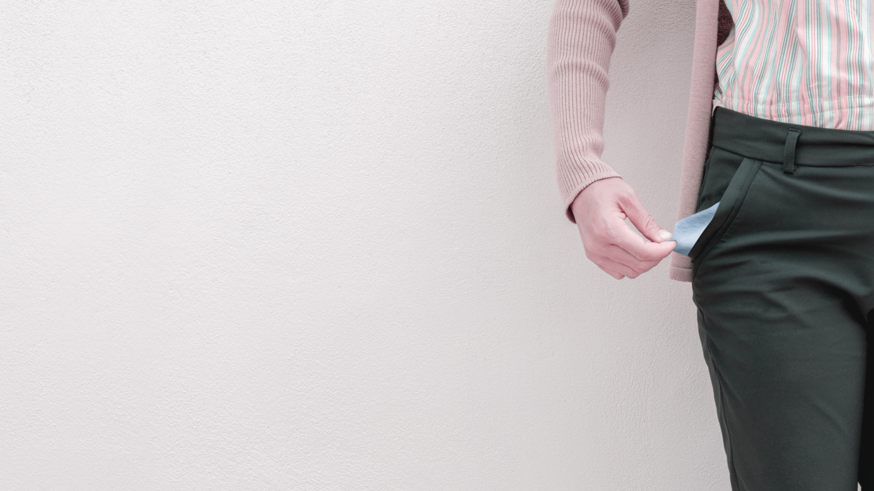 Woman showing her empty pocket on wall background.
