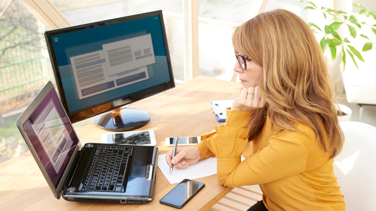 Thinking businesswoman working at office while sitting in front laptop and computer.