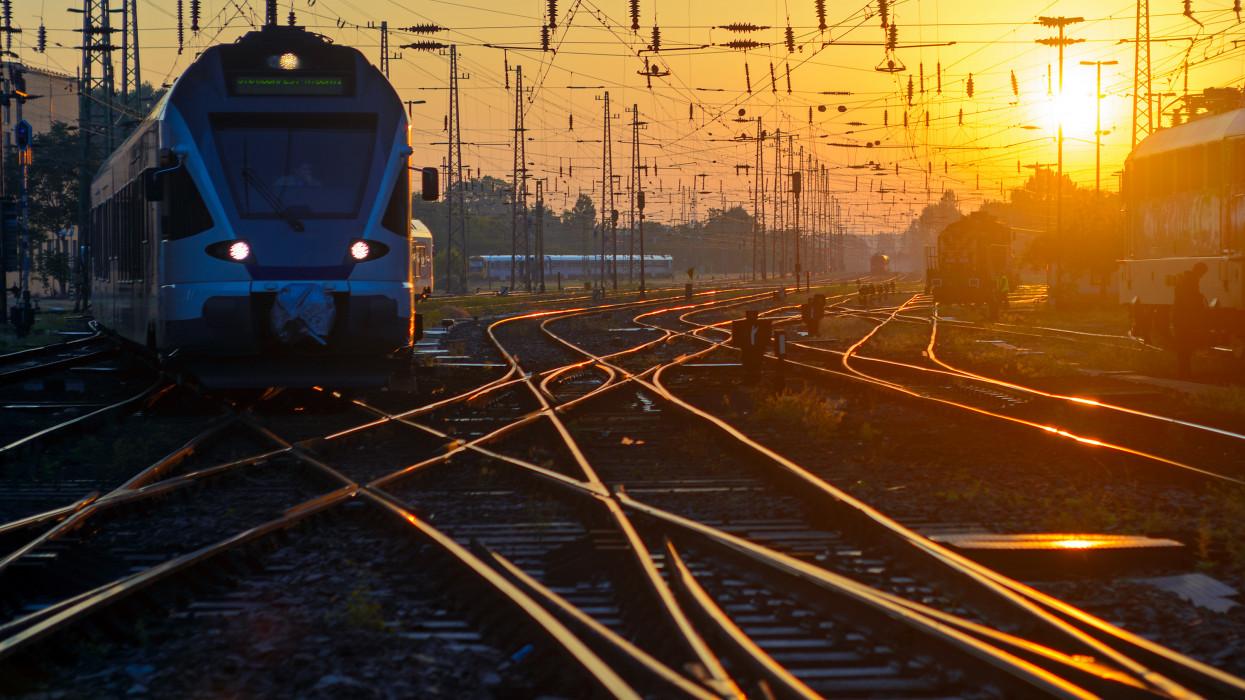 Sunrise, railroad junction, sunlit rails, frontal view of the train