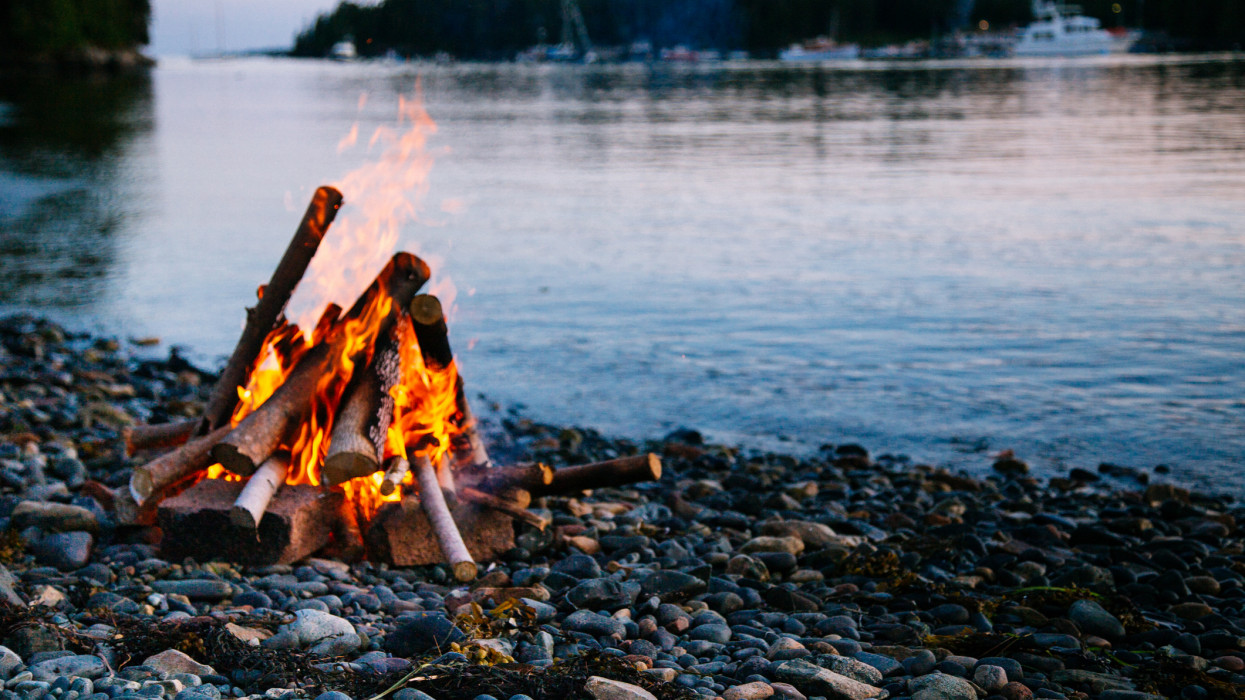 Lighting a beach fire at dusk along the water is a popular activity during the summer in Maine.
