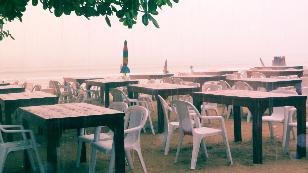 Empty tables of an open-air cafeagainst the cloudy sky and grayish sea. The weather was easily bad and it rained suddenly,  low season so tourist business idles.