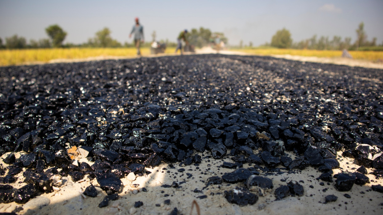 Close-up shot of a Road under construction with koltaar and pebbles seen covered in black Molten koltaar.