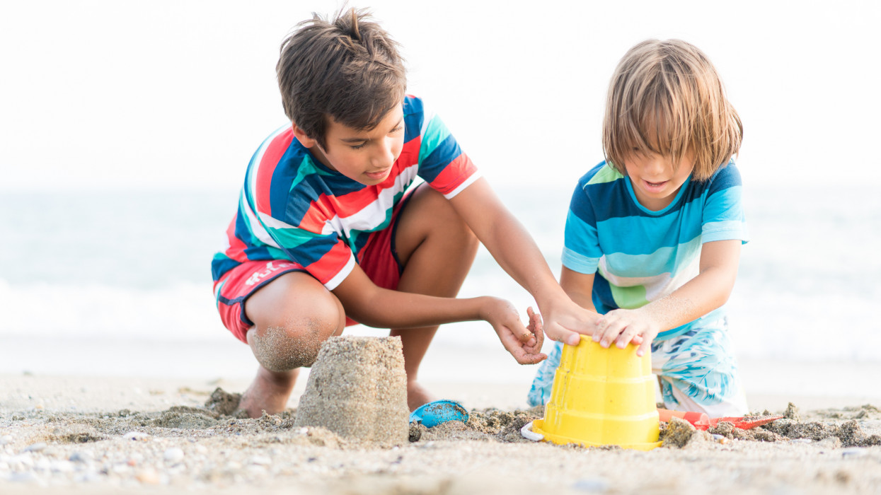 Two Boys on Beach Playing and Building Sandcastle